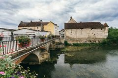 Lake in Chablis, Burgundy. Landscape of a medieval French town, over a lake stone bridge with flowers Chablis, France. July 22, 2017 stock photo