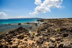 Landscape of the Mediterranean coast in an island, with rocks, sea and a sky with some clouds. In a sunny day royalty free stock image