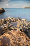 Landscape of the Mediterranean coast with rocks in the foreground and some vessels in the background. Landscape of the Mediterranean coast with rocks in the Royalty Free Stock Images