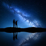 Landscape with Milky Way. Silhouette of a father and son. Milky Way with silhouette of a family. Father and a son who pointing finger in night starry sky on the royalty free stock photography