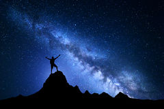 Landscape with Milky Way and silhouette of a happy climber Stock Photos