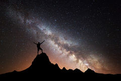 Landscape with Milky Way and silhouette of a happy man Royalty Free Stock Photos