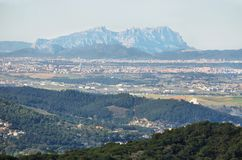 Montserrat multi-peaked mountain at background and towns in the surrounding area Royalty Free Stock Photography