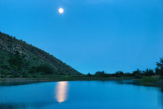Landscape with moon above the lake Royalty Free Stock Photos