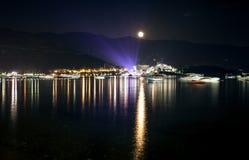 Landscape of moon shining over seaside city at dark night Royalty Free Stock Photos