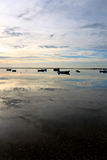 Landscape morning. Wideview of an early morning with lush fluffy cloud sky with several fishing boats and reflection on the water Stock Images