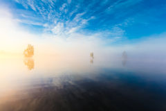 Landscape of morning nature on lake with blue sky, clouds,  fog mist and lonely tiny islands Stock Images