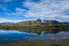 Landscape of mountain, lake and treeline under blue sky, tibet. Stock Photo