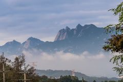 Mountain peak surrounded by fog and morning mist. Landscape of mountain peak surrounded by fog and morning mist Royalty Free Stock Photos