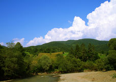 Landscape at the mountain with river. Landscape image at the mountain, with a blue sky and white clouds and little river royalty free stock photos