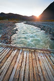 Landscape mountain river and a wooden bridge at sunset. Stock Image
