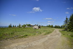 Landscape of mountain road and wooden houses. Royalty Free Stock Photos