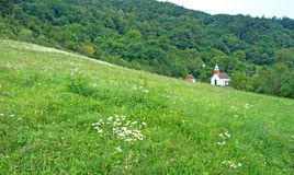 Landscape of mountain slope with white country church, Serbia Stock Photo