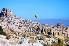 Landscape of mountainous terrain in Cappadocia. In Turkey and yellow balloon over the mountains Royalty Free Stock Images