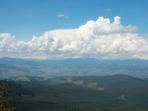 Landscape of mountains and cloudy sky. Carpathians mountains, west Ukraine. Big white cumulus flowing in blue sky. Ukrainian nature background. Green hillsides royalty free stock image