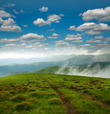 Landscape of mountains on the horizon, under white clouds. On background blue sky, beauty of nature Royalty Free Stock Images