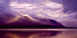Landscape. Mountains and lake in mist in morning with purple col Royalty Free Stock Images