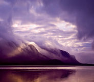 Landscape. Mountains and lake in mist in morning with purple color