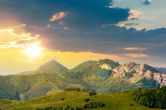 Landscape in mountains with rocky formations. Grassy meadows, forested hills and huge cliffs. wonderful nature scenery. beautiful weather at sunset in royalty free stock photography