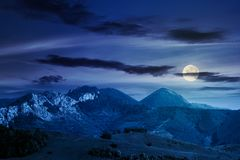 Landscape in mountains with rocky formations. Grassy meadows, forested hills and huge cliffs. wonderful nature scenery. beautiful weather at night in full moon royalty free stock photo