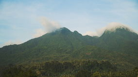 Landscape of mountains and sky.Camiguin island. Mountains landscape, rainforest, jungle, blue sky, clouds and mist. Volcano on the island of Camiguin. Travel stock footage