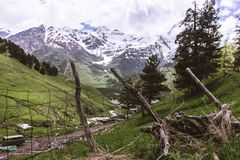 LANDSCAPE OF MOUNTAINS IN SNOW WITH FENCE, GREENS AND CLOUDY SKY royalty free stock photography