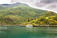 Landscape in Norway. Landscape with Naeroyfjord, ship, mountains, traditional houses and dark clouds in Norway Royalty Free Stock Image