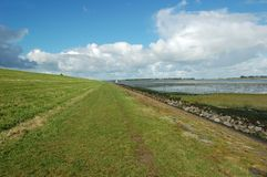 Landscape nature reserve dike. The slope of a dutch dike an the landscape of nature reserve Oosterschelde, with salt marsh at ebb tide on a sunny day Stock Image