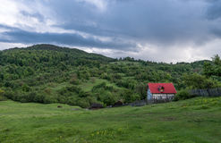 Landscape Nature in Romania. Mountain and Cloudy Sky. Lonely House with Red Roof Stock Image