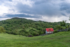 Landscape Nature in Romania. Mountain and Cloudy Sky. Lonely House with Red Roof Royalty Free Stock Photography