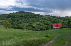 Landscape Nature in Romania. Mountain and Cloudy Sky. Lonely House with Red Roof Royalty Free Stock Photo