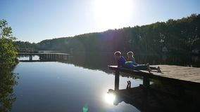 Landscape near the lake. Reeds and mother with daughter on the pier. stock footage