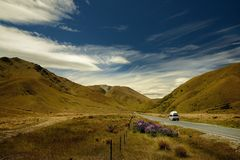 Landscape New Zealand - South Island - landscape near Southern Alps - road between mountains, blue sky with clouds. Hills and road stock photo