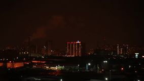 Landscape of night city with high-rise buildings under construction, factories and pipes of which there is smoke stock video
