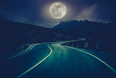 Landscape of nighttime with curvy roadway at national park. Cross process and dark tone. Landscape of full moon with curvy roadway in forest at national park royalty free stock photo