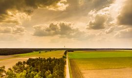 Landscape in the North German Heath near Celle, with a small piece of forest, meadows, fields and a TV tower on the horizon, drama royalty free stock photos