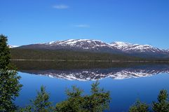 Landscape in Norway. Mountains refection i a blue mountain lake Royalty Free Stock Photo