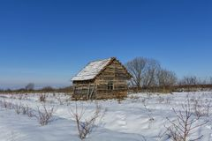 Landscape of old abandoned farm house covered with snow in a frosty winter. Royalty Free Stock Image