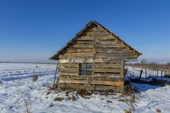Landscape of old abandoned farm house covered with snow in a frosty winter. Stock Photos