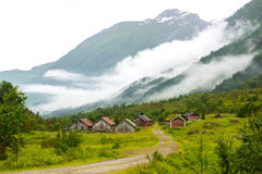 Landscape with old wooden houses and mountains covered by clouds, Norway. Landscape with old wooden houses in the forest and mountains covered by clouds, Norway Royalty Free Stock Images