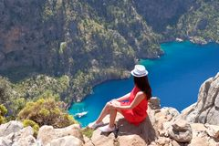 Landscape Oludeniz, Turkey, a young girl in a red dress looks at the Butterfly Valley from above, sitting on the rocks.  stock images
