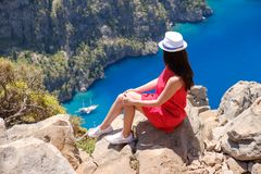 Landscape Oludeniz, Turkey, a young girl in a red dress looks at the Butterfly Valley from above, sitting on the rocks.  stock photo