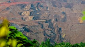 Landscape of open pit coal mining in Sangatta, Indonesia. Open pit coal mining in Sangatta, Indonesia with green vegetation as the foreground stock image