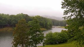 Landscape of outdoors green trees grass lake mist mountain stock photos