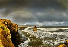 Reynisdrangar, rainbow after rain, Iceland. Offshore lie stacks of basalt rock, remnants of a once more extensive cliffline Reynisfjall, now battered by the sea stock image