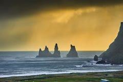 Reynisdrangar, stacks of basalt rock, sunset after rain, Iceland. Offshore lie stacks of basalt rock, remnants of a once more extensive cliffline Reynisfjall stock photo
