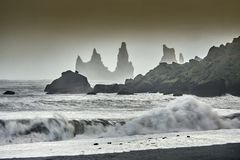 Reynisdrangar, stormy waves, autumn 2018, Iceland. Offshore lie stacks of basalt rock, remnants of a once more extensive cliffline Reynisfjall, now battered by royalty free stock photo