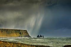 Reynisdrangar, stacks of basalt rock, autumn 2018, Iceland. Offshore lie stacks of basalt rock, remnants of a once more extensive cliffline Reynisfjall, now royalty free stock image