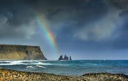 Reynisdrangar, stacks of basalt rock, rainbow, autumn 2018, Iceland. Offshore lie stacks of basalt rock, remnants of a once more extensive cliffline Reynisfjall stock photography