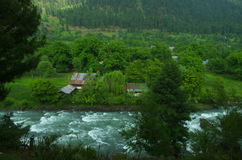 Landscape in Pahalgam-6. A beautiful scene in the season of a monsoon showing lush green fields and river water flowing with force Royalty Free Stock Photo